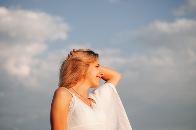 Uma bela mulher no contexto de nuvens em foto romântica de perfil de um jovem sorriso feliz ...