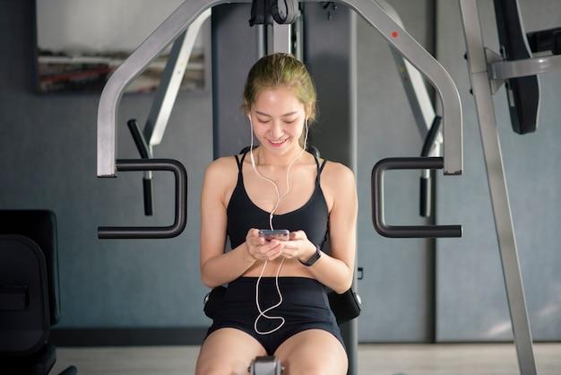 Uma bela mulher sorridente em fones de ouvido usando uma rede social e ouvindo música na academia, fitness e conceito de tecnologia