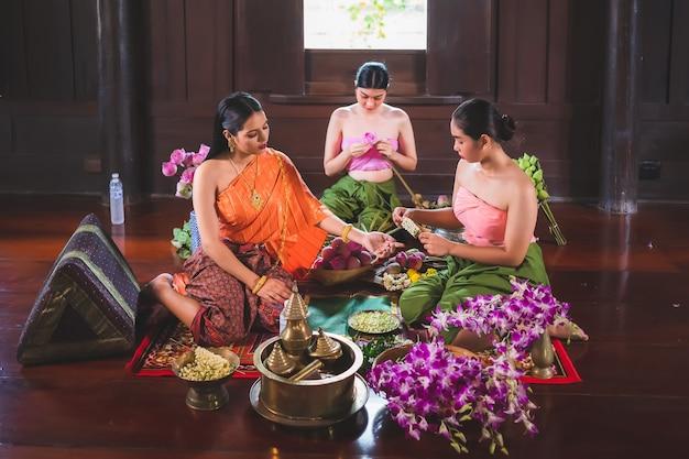 Uma bela mulher tailandesa e ela usa trajes tradicionais tailandeses, ambos mestres e servos. eles estão sentados preparando flores em uma casa de madeira para fazer mérito no dia do buda.