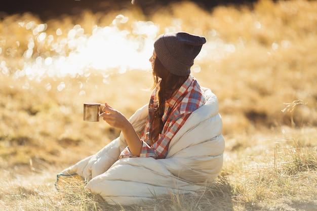 Uma bela mulher viajante caminhando nas montanhas com um copo de bebida perto do lago.