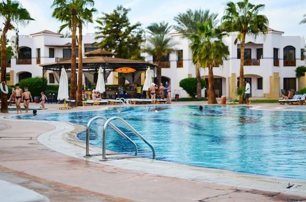 Uma bela piscina de água azul no meio de um hotel pitoresco.