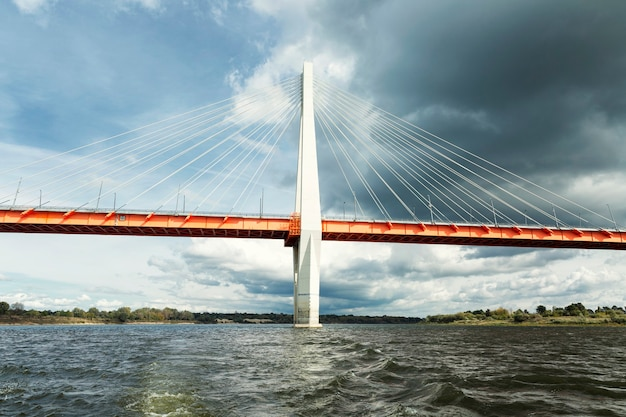 Uma bela ponte estaiada sobre o rio, tendo como pano de fundo um céu nublado e sombrio. paisagem bonita.