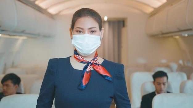 Uma bela tripulação de cabine asiática está usando máscara protetora a bordo