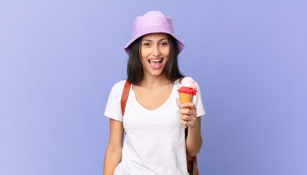 Uma bela turista hispânica, feliz e agradavelmente surpresa, segurando um sorvete