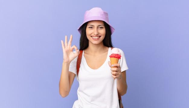 Uma bela turista hispânica se sentindo feliz, mostrando aprovação com um gesto de ok e segurando um sorvete