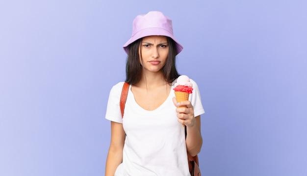 Uma bela turista hispânica se sentindo perplexa e confusa e segurando um sorvete
