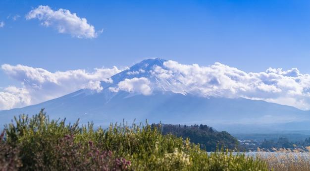 Uma bela vista completa da montanha fuji com neve e nuvens cobrindo o topo.