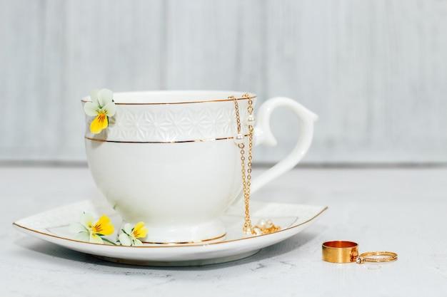 Uma bela xícara branca com uma borda dourada, decorada com flores e joias de ouro. projeto de conta comercial.