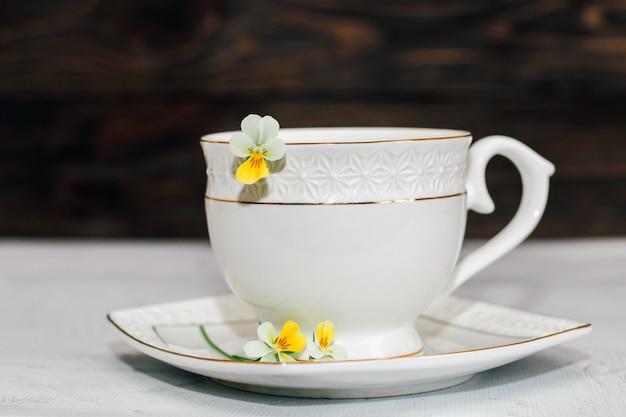 Uma bela xícara branca com uma borda dourada decorada com flores. projeto de conta comercial.