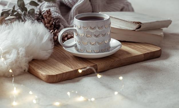 Uma bela xícara com uma bebida quente em uma bandeja de madeira. conceito de conforto em casa.