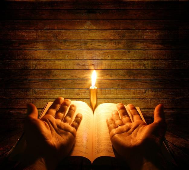 Uma bíblia aberta em uma mesa ao lado de uma vela