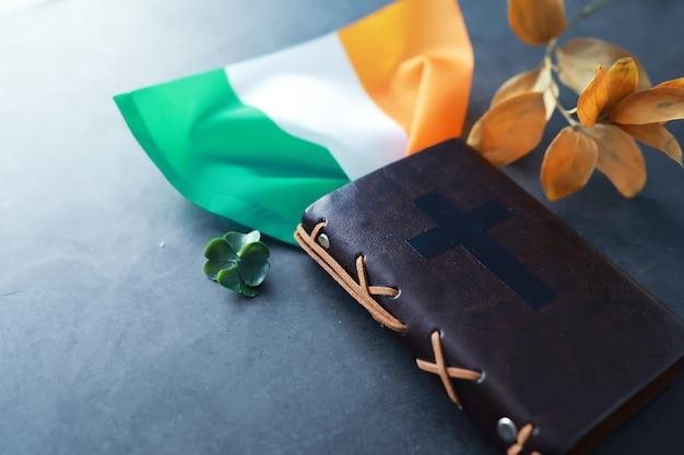 Uma bíblia encadernada em couro sobre a mesa. celebração religiosa cristã irlandesa. símbolo do trevo de quatro folhas de boa sorte.