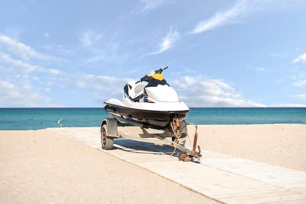 Uma bicicleta aquática esportiva jetski no trailer na praia de areia no verão nas férias
