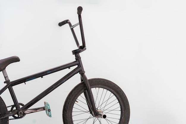 Uma bicicleta bmx preta perto da parede, equipamentos para esportes radicais