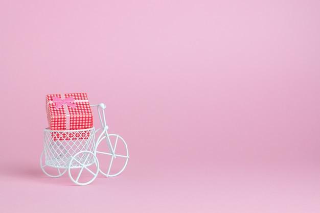 Uma bicicleta de brinquedo carrega um presente. a ideia para um cartão postal.