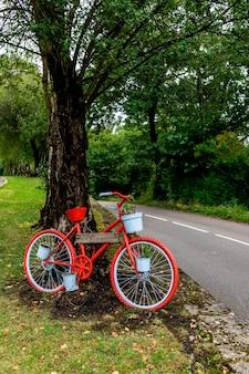 Uma bicicleta de ornamento vermelho pitoresca e bonita em uma árvore ao lado de uma estrada