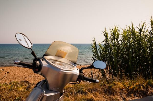Uma bicicleta de scooter prata genérica está estacionada à beira-mar.