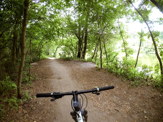 Uma bicicleta fica em um caminho de terra na floresta. o conceito de turismo, recreação. copie o espaço.