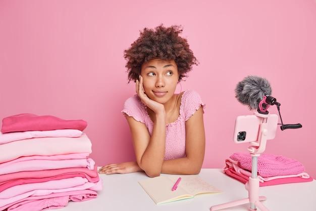 Uma blogueira afro-americana pensativa grava um vídeo tutorial sobre como lavar a roupa corretamente, senta-se à mesa com pilhas de cadernos de roupas dobradas abertas isoladas sobre rosa