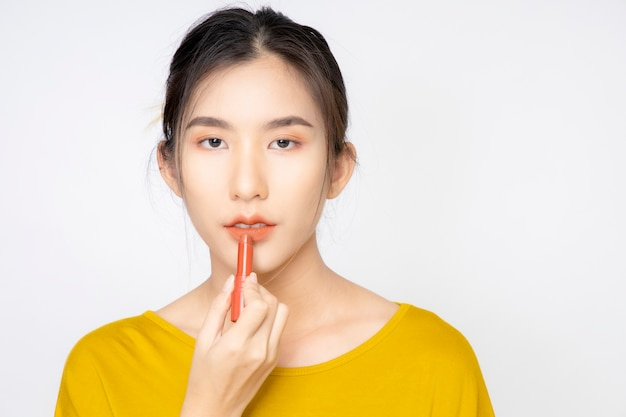 Uma blogueira asiática, blogueira de beleza, gravando um vídeo dela mesma usando um batom laranja em um estúdio.