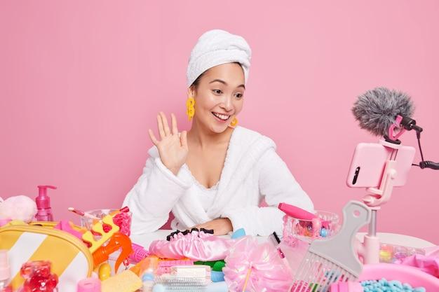 Uma blogueira asiática de beleza feminina sorridente filmes tutorial de maquiagem acenando olá na câmera do smartphone
