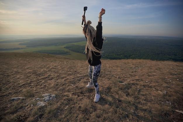 Uma blogueira com longas tranças leves fica no topo de uma montanha com uma câmera erguida contra a ...