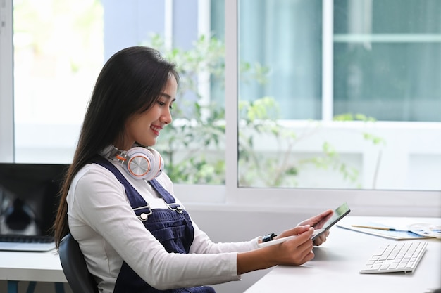 Uma blogueira em fones de ouvido durante o trabalho freelance em um computador tablet em seu local de trabalho.
