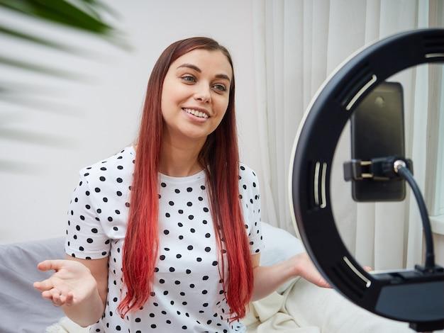 Uma blogueira fofa está transmitindo online em casa usando uma lâmpada de anel. a mulher se comunica com os assinantes, gesticula com as mãos.
