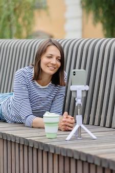 Uma blogueira ou profissional de marketing jovem e confiante se comunica com seu público ou conduz um show ao vivo