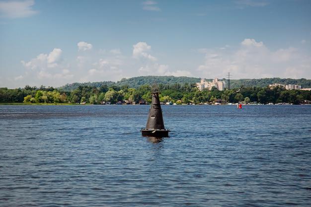 Uma bóia preta em uma superfície de água calma. sinal de aviso na água em um dia ensolarado.