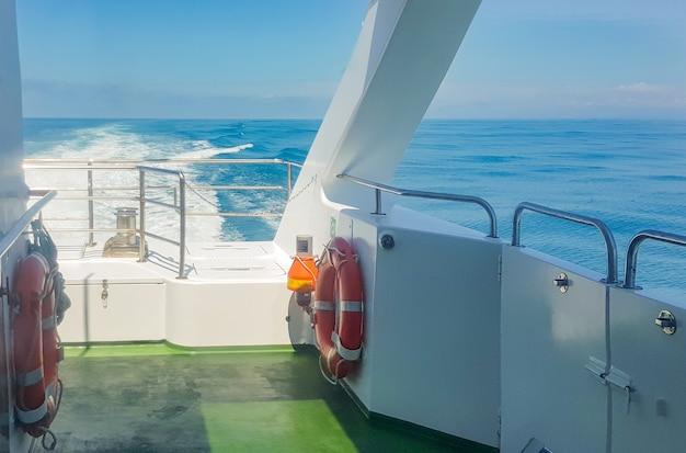 Uma bóia salva-vidas no convés de um iate de luxo, vista para o mar com ondas, trilha na água, conceito de férias na água e viagem romântica