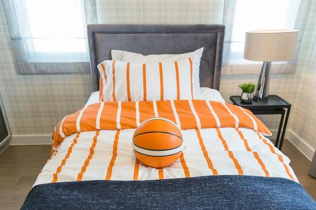 Uma bola de basquete na cama com lâmpada de cabeceira no quarto crianças