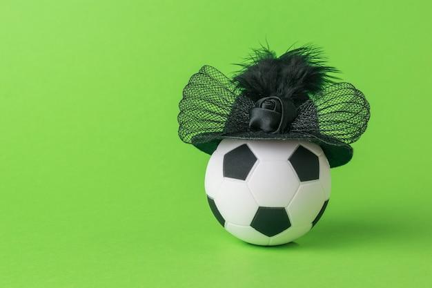 Uma bola de futebol com um elegante chapéu sobre um fundo verde. o conceito de futebol feminino.