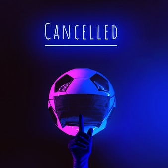 Uma bola de futebol com uma máscara médica preta do vírus. mão na luva com o dedo levantado. à luz do neon em um fundo escuro