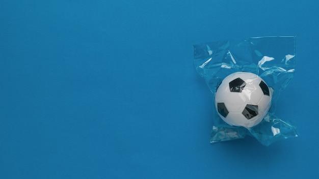 Uma bola de futebol em um pacote de celofane sobre um fundo azul. lugar para texto.