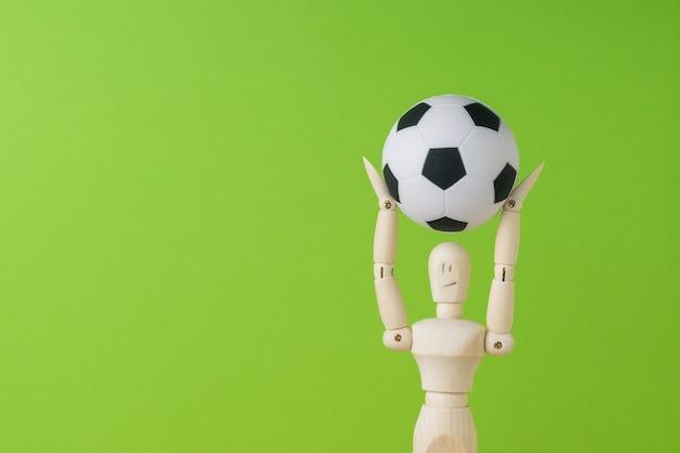 Uma bola de futebol nas mãos de um homem de madeira sobre um fundo verde. espaço para texto.