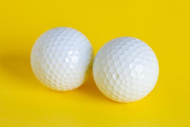 Uma bola de golfe branca isolada em amarelo, esporte