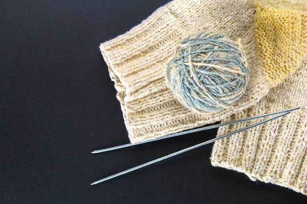 Uma bola de lã com agulhas de tricô e meias em uma mesa cinza. bordado