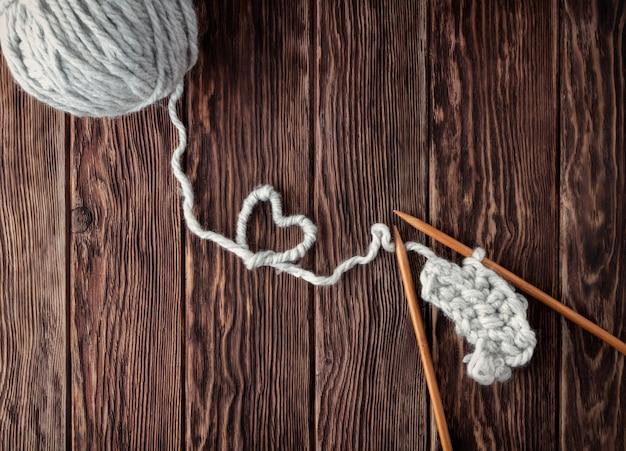 Uma bola de linha e agulhas de tricô em um fundo de madeira. conceito artesanal e bordado.