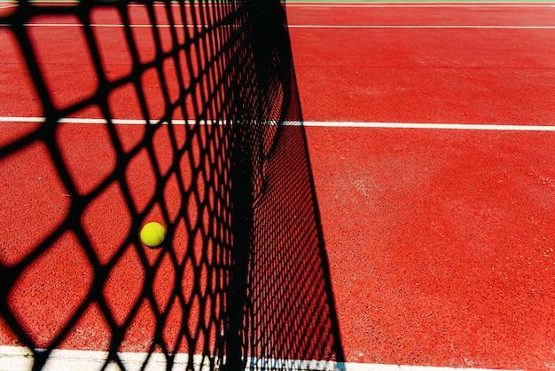 Uma bola de tênis no chão texturizado de uma quadra vermelha perto da rede depois de perder um match point.