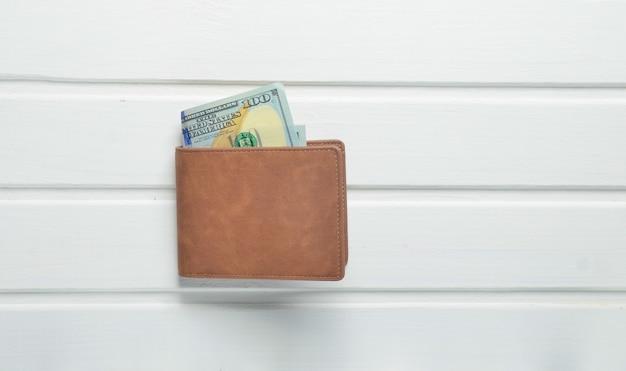 Uma bolsa com notas de dólar em uma mesa de madeira branca. vista do topo.