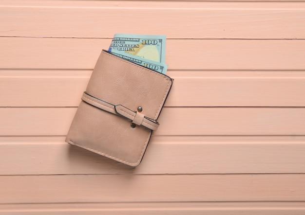 Uma bolsa com notas de dólar em uma mesa de madeira rosa. vista do topo.