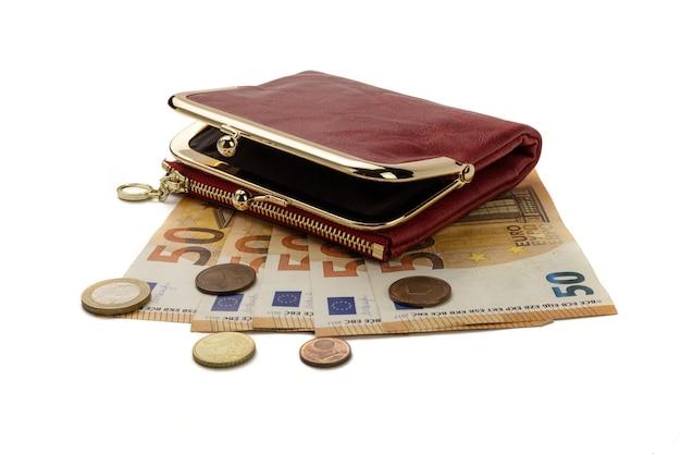 Uma bolsa vermelha sobre notas e moedas de cinquenta euros, isolada