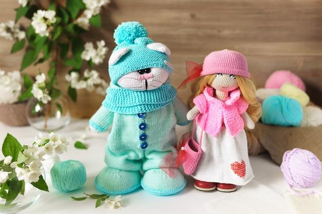 Uma boneca e um gato feitos de fio de lã. brinquedo de pelúcia de malha artesanal sobre uma mesa de madeira.