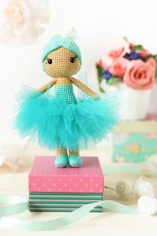 Uma boneca feita de fio de lã. brinquedo de pelúcia de malha artesanal sobre uma mesa de madeira.
