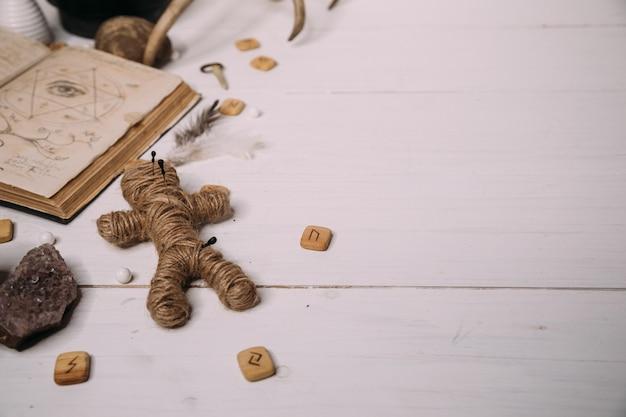 Uma boneca vodu feita de corda encontra-se com um grimório de livro antigo