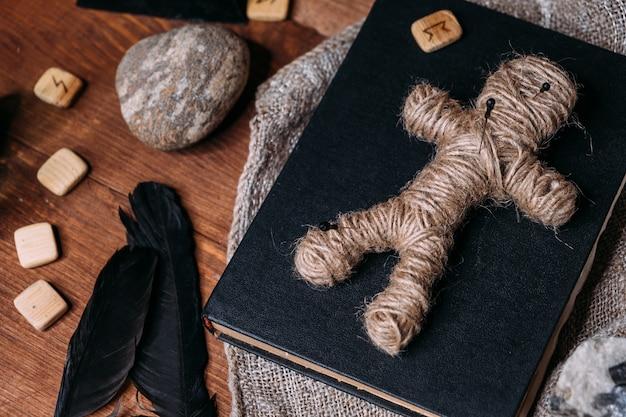 Uma boneca vodu feita de corda repousa sobre um livro preto, cercada por objetos rituais mágicos, deitada de lado