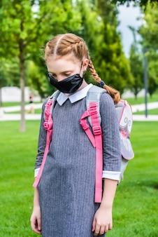 Uma bonita colegial com cabelos ruivos e máscara médica vai para a escola. ela está triste, ofendida porque está ofendida. uma mochila escolar, na cabeça há duas tranças. ruiva