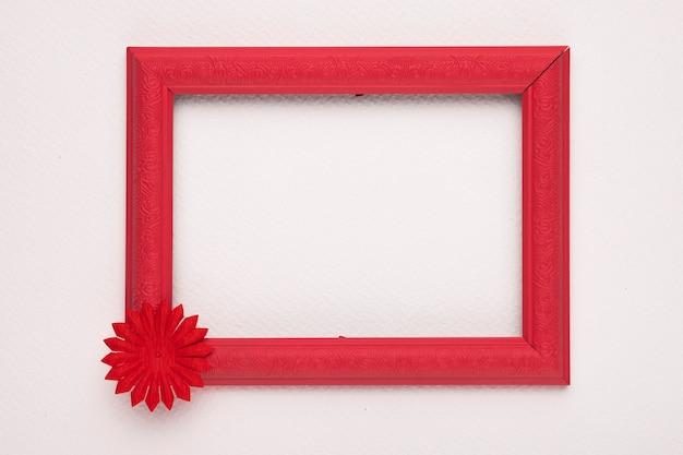 Uma borda vermelha de madeira vazia com flor na parede branca