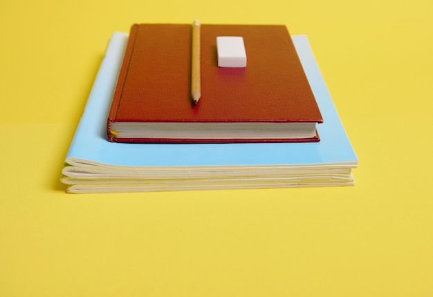 Uma borracha, lápis em um livro com capa dura, livros didáticos, isolado em fundo amarelo com espaço de cópia